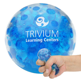 trivium learning center logo on large bead stress ball in background and hand squeezing stress ball in foreground