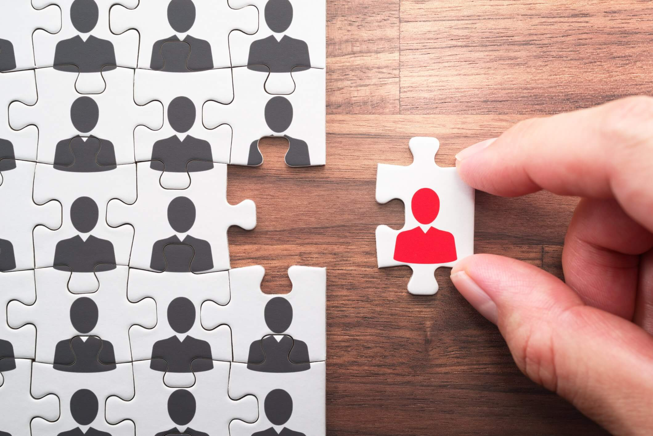 A Guide to Recruitment Marketing Strategies on a Small Budget outline of figure on puzzle pieces with one red outlined figure on missing piece
