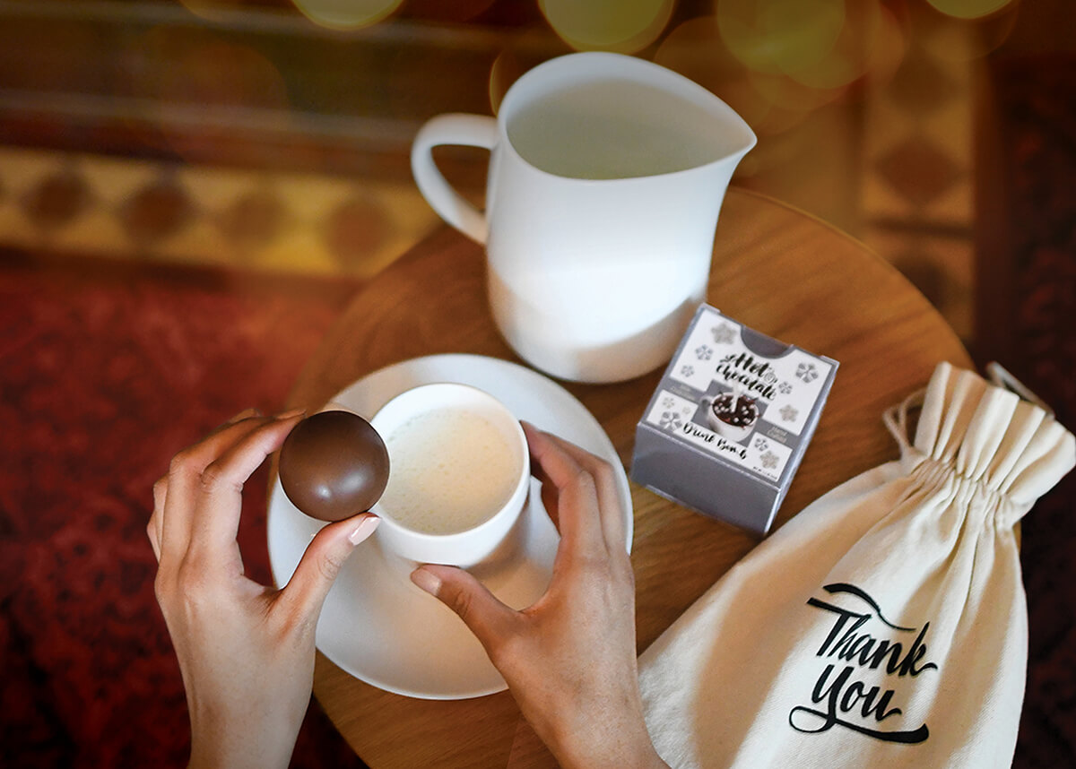 Two hands holding a hot chocolate bomb over a hot cup of milk with a white pitcher and thank you drawstring bag.